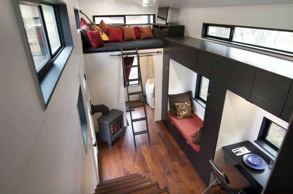 hOMe tiny home interior with wood stove, window seat, table for one and loft.