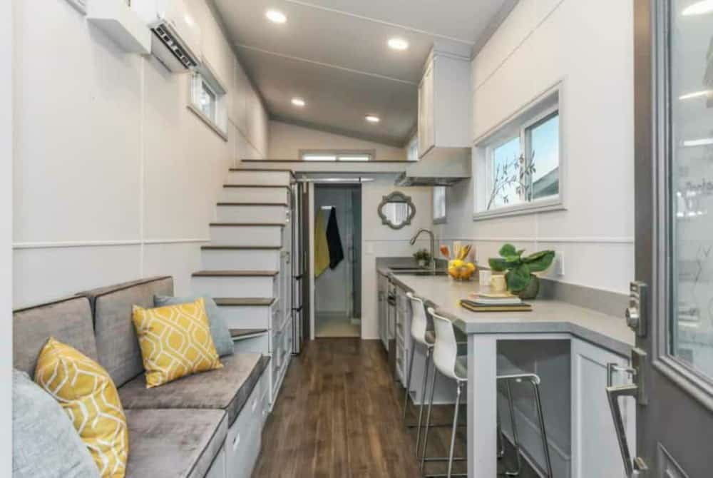 Interior of the Modern Tiny House, the last on the list of tiny homes for sale in Texas, shows modern white and grey decor with couch, loft and dining bar.