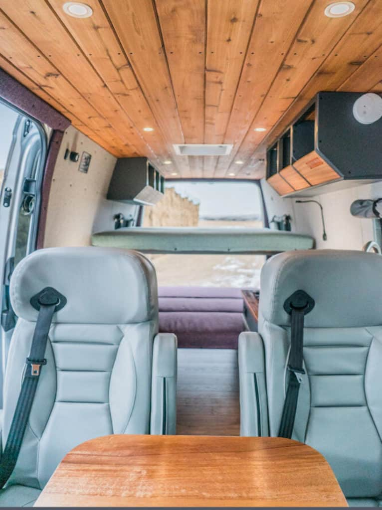 Interior of a custom Sprinter van camper with view from the front, including wood paneled ceiling and platform bed
