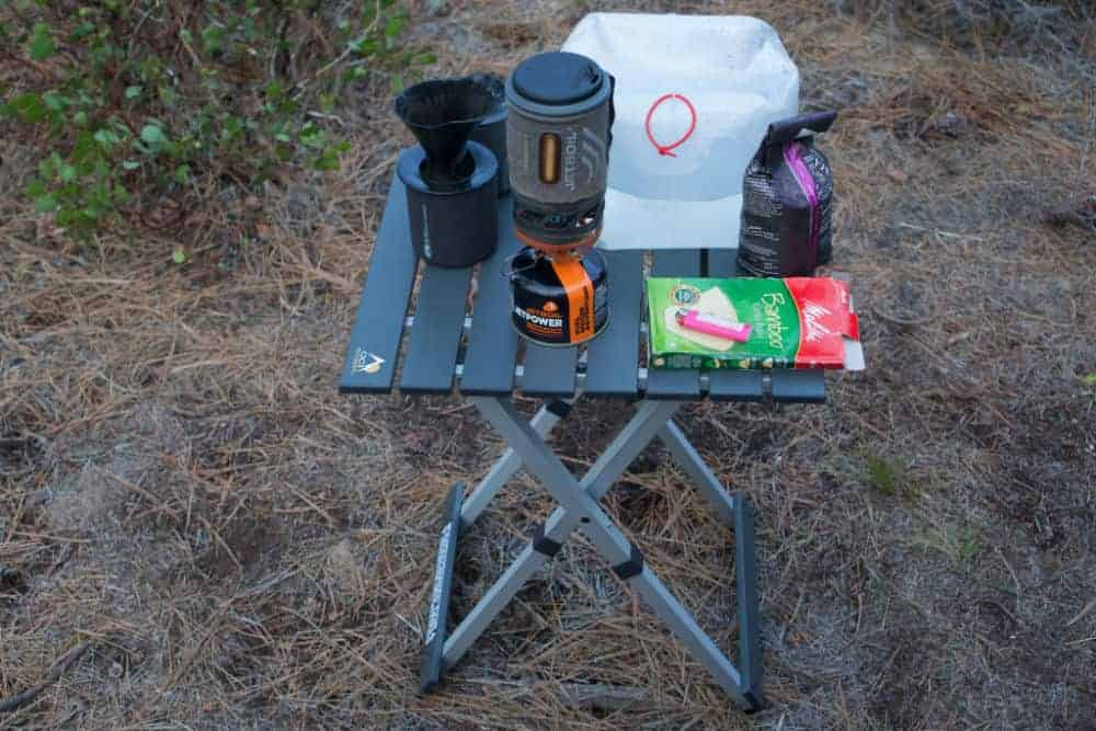 A camping table showing all my favorite boondocking gear, including a cookstove and collapsible water container.