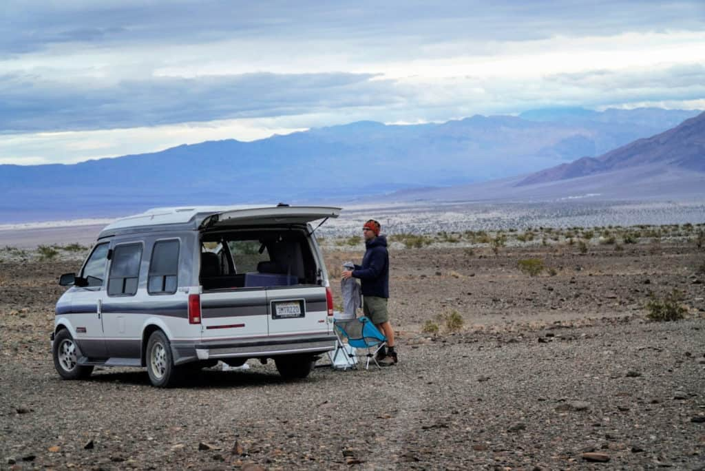 Tom standing by the van in a gorgeous boondocking campsite in Death Valley