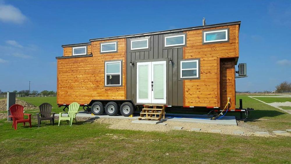 The Freedom tiny house for sale in Texas sits on green grass with a clear blue sky above.