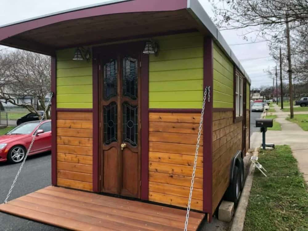The Gypsy Wagon tiny home has wood paneling on the bottom, green siding on top.