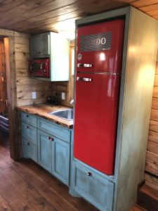Interior kitchen view of the Gypsy tiny home shows wooden cabinets and a bright red fridge.