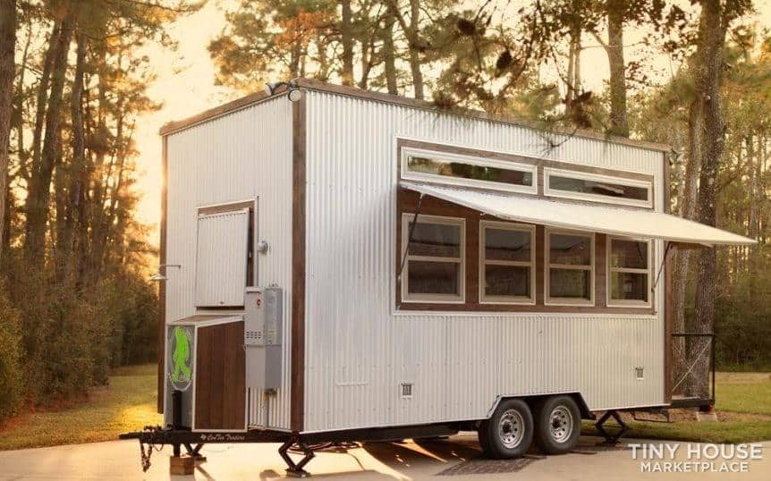 The Rustic Tiny house with metal siding and raised awning, parked near the woods.