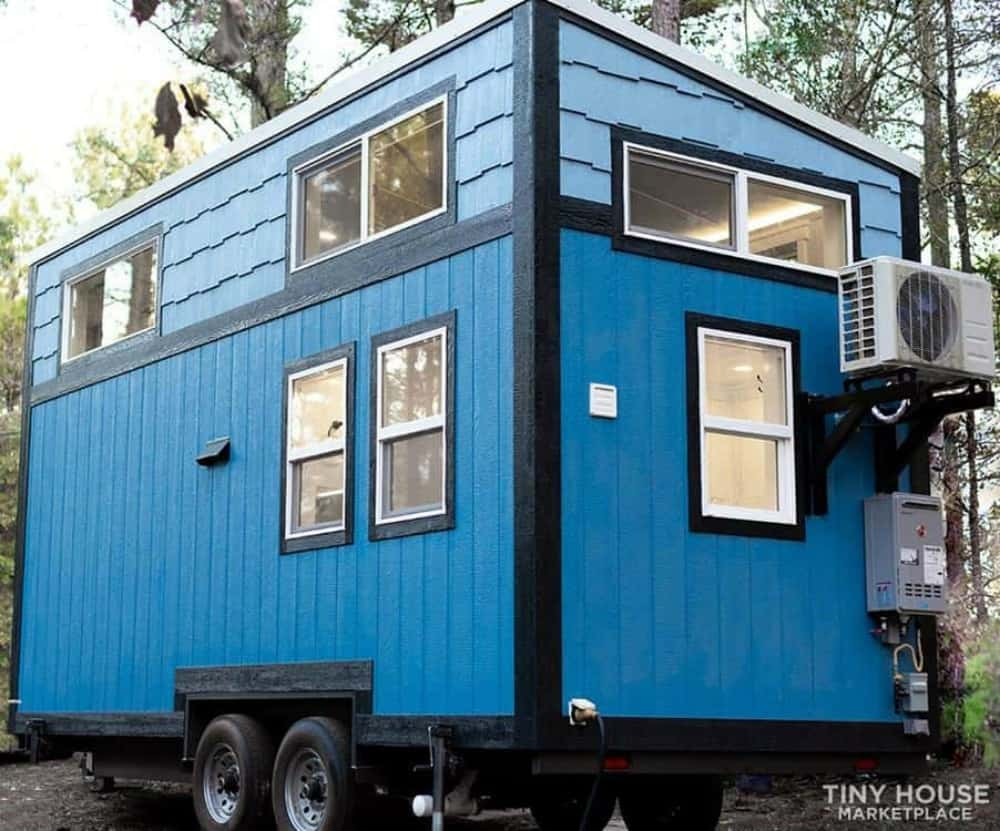 The Bluejay tiny house with woods in the background is one of the tiny houses for sale in Texas.