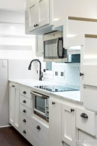Bluejay all white kitchen interior with stainless steel appliances.