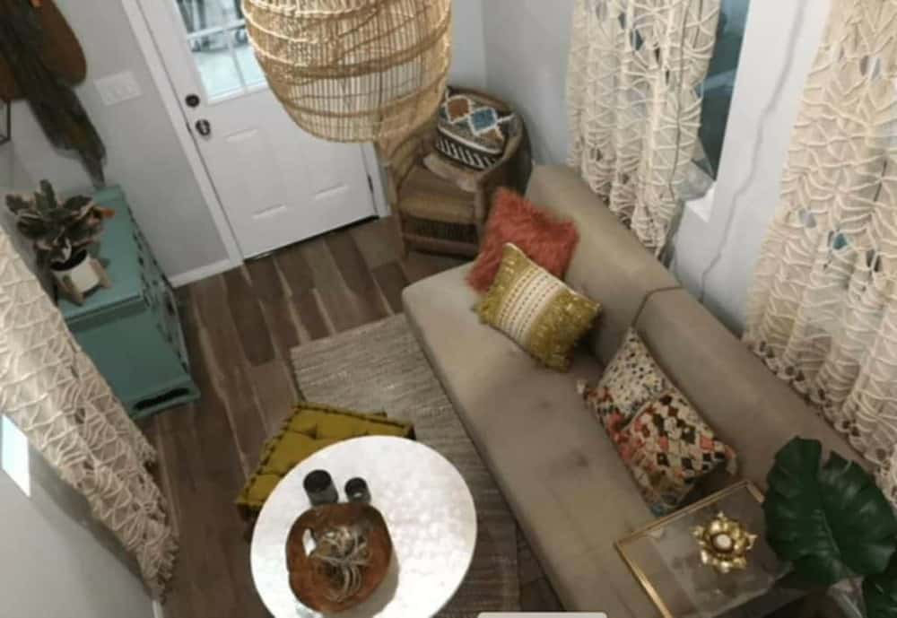 Interior view of the Tiny Cottage shows cozy living room furniture, light wooden floors and floor to ceiling curtains.