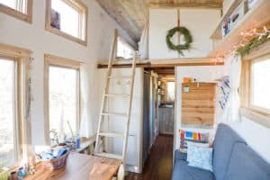 Interior of The Tiny Project Home showing ladder leading up to loft above short hallway.