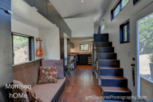 hOMe tiny house interior view of stairs, kitchen and couch.