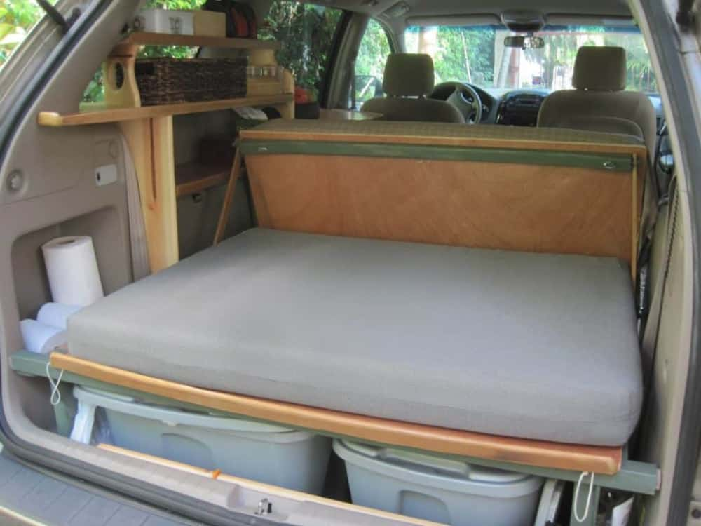 View into the back of Glenn's minivan camper shows bed with storage underneath and two car seats in the front.