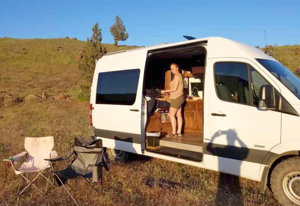 woman cooking in a Sprinter van camper rental