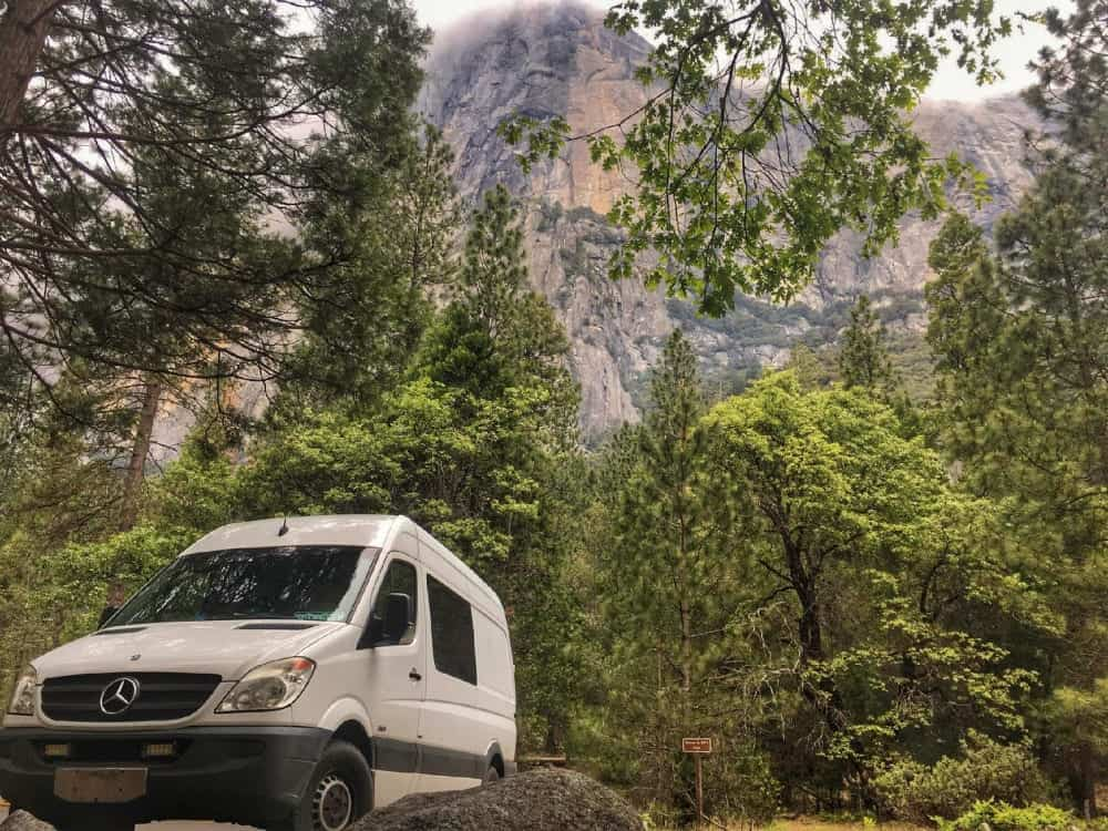 The Rabbit Hole Sprinter Camper Van with forest and mountain in background.