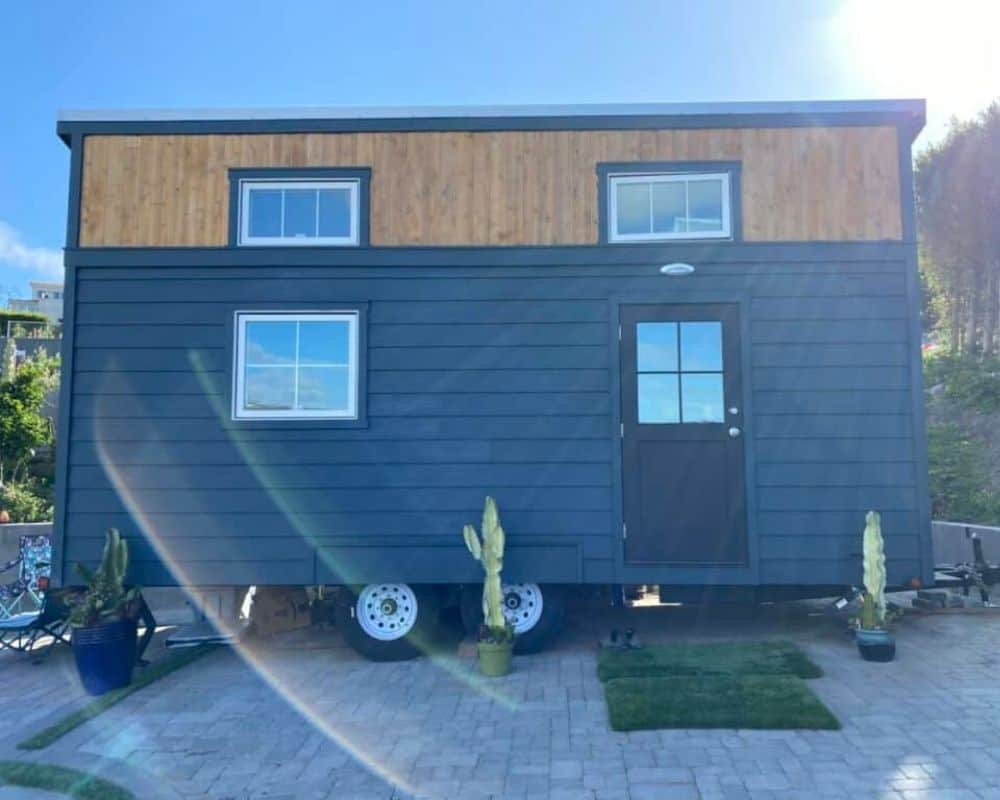 Roanoke tiny home for sale in California parked on brick lot with blue sky in the background.