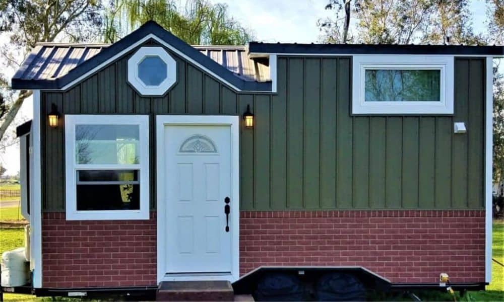 The Evergreen tiny house, for sale in California has green siding on the top 2/3rds, red brick on the bottom 1/3rd and white door and trim.