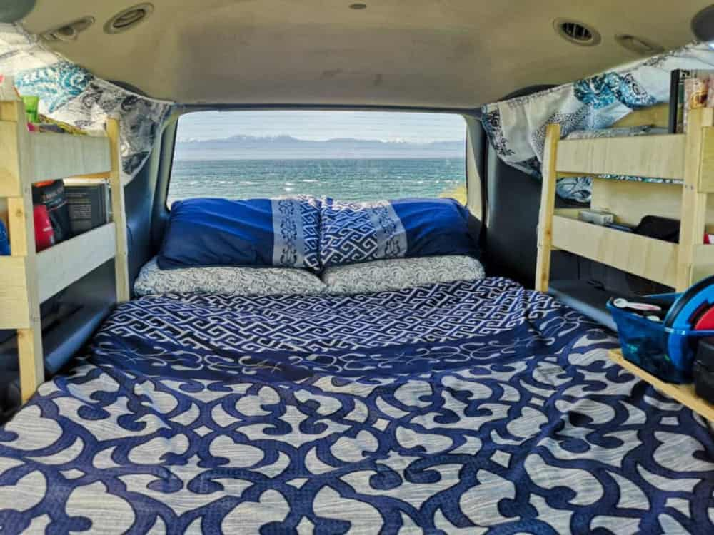 A bed, with wooden shelving on either side, fills the interior space of this Dodge Grand Caravan minivan camper.