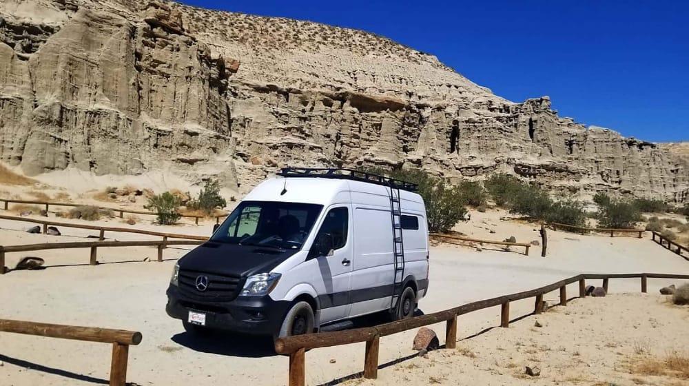 Vigos Sprinter van on a dirt road near rocks