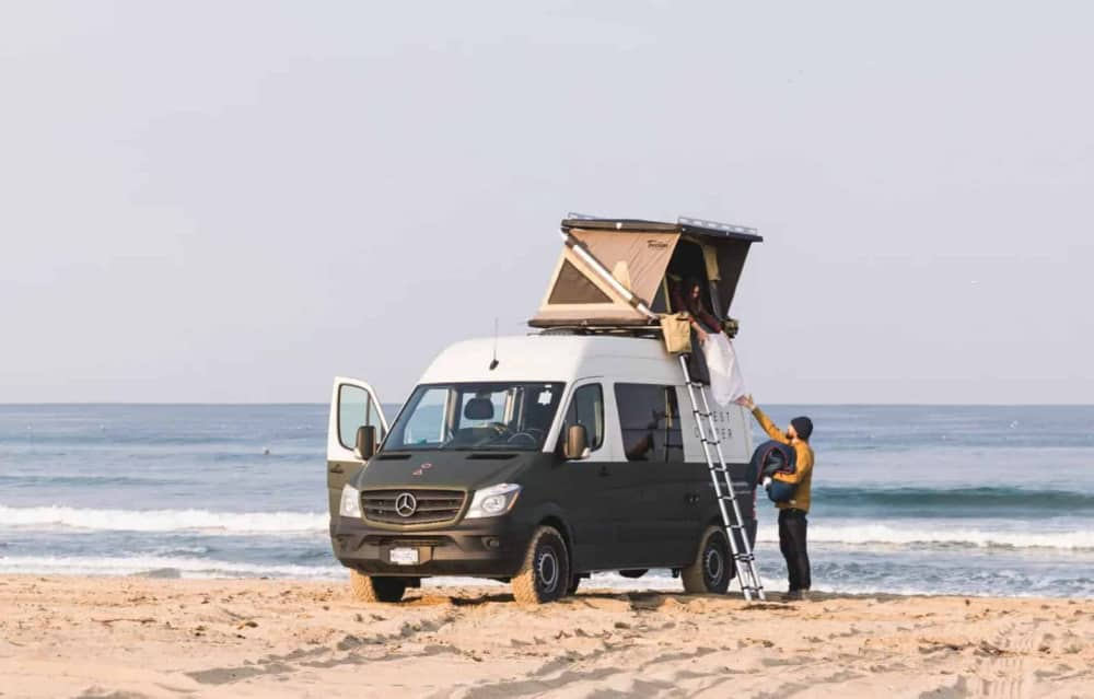 sprinter van rental parked on the beach with a rooftop tent