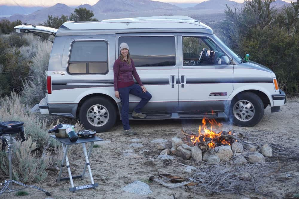 Kristin standing in front of her Chevy Astro van with a campervan cooker on a small folding table.