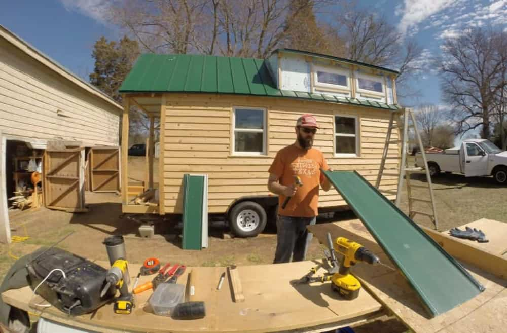 Man looks at metal roofing sheet in front of partially roofed DIY tiny house.