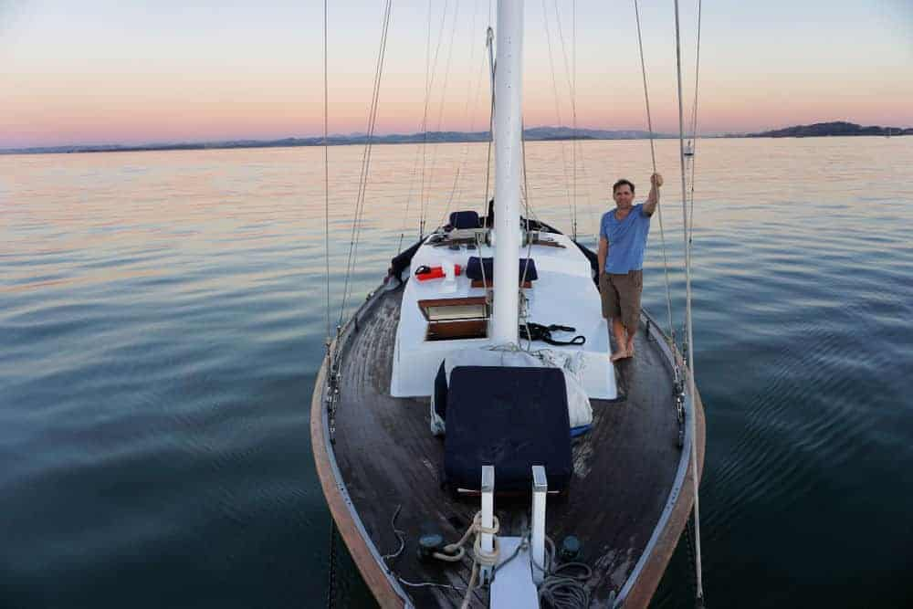 a liveaboard sailboat floating in the water with a man onboard