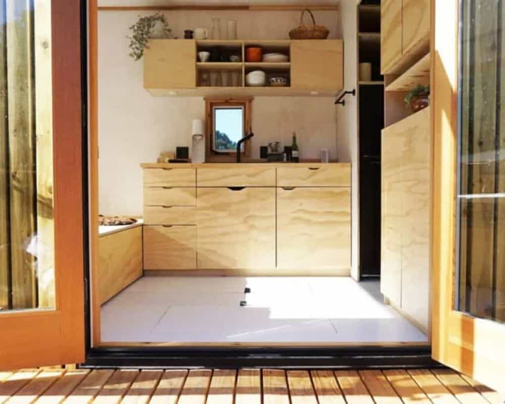 View through double doors into kitchen of Namu Haus tiny home for sale in California.