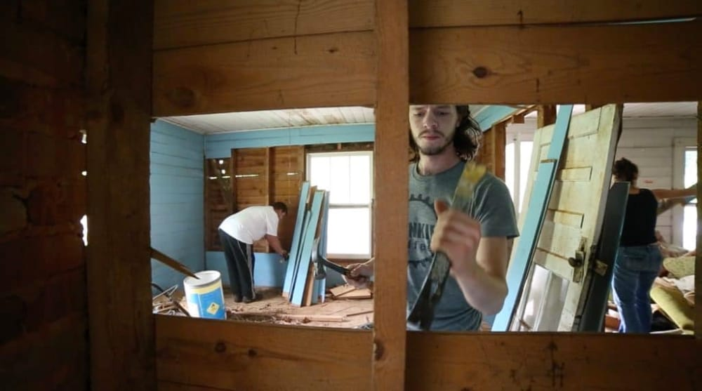 3 people work to deconstruct vacant farmhouse and salvage wood to build their own tiny home