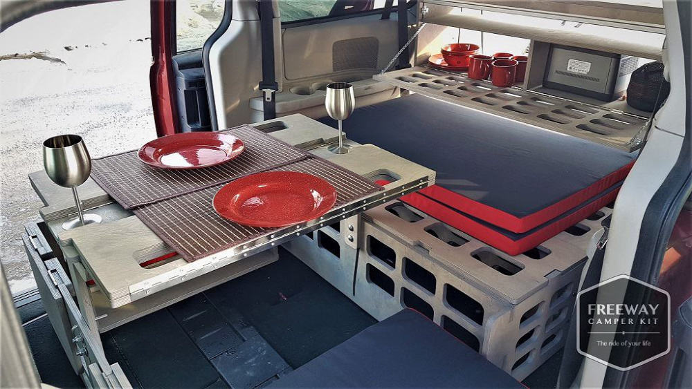 Interior view of minivan converted with Freeway camper kit shows dish storage, and a multi functional folding table with set for a meal.