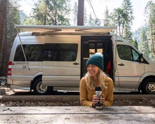 Sprinter camper van rental with woman sitting at a picnic table with coffee