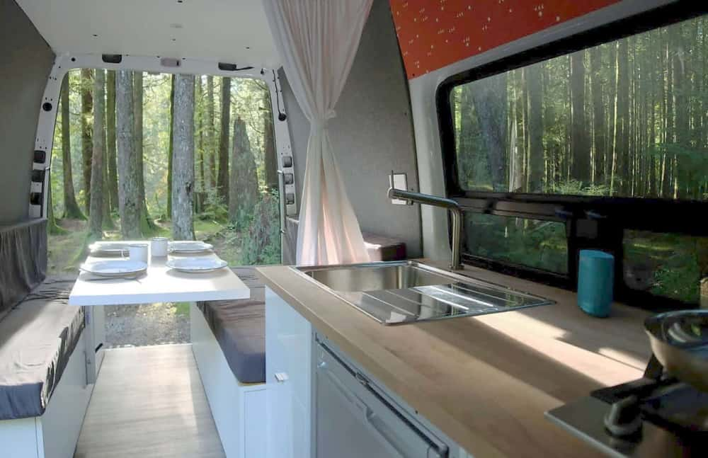 Interior of a Sprinter camper van rental with kitchen and table