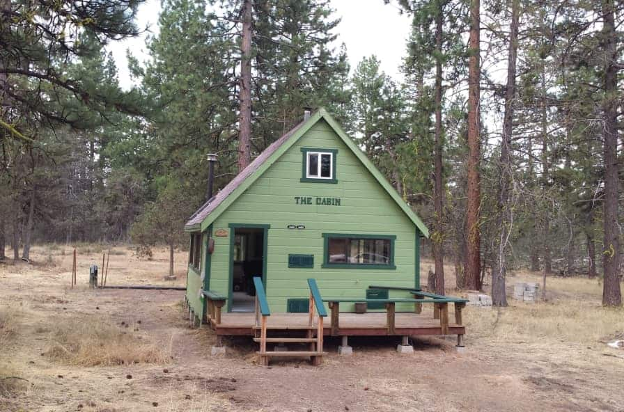 Green off grid cabin tiny home for sale in California, sits on dry ground with trees surrounding.