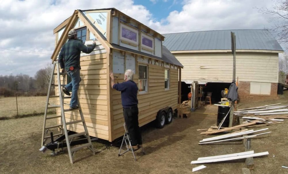 Two men building their own tiny house, adding siding in a yard