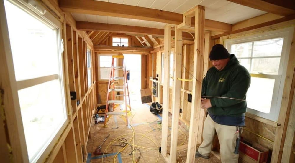 An electrician works on wiring in the shell of a DIY tiny house.