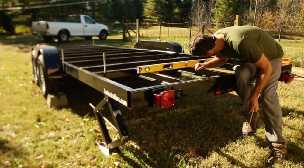 Man looks at level on tiny house trailer to confirm it is level.