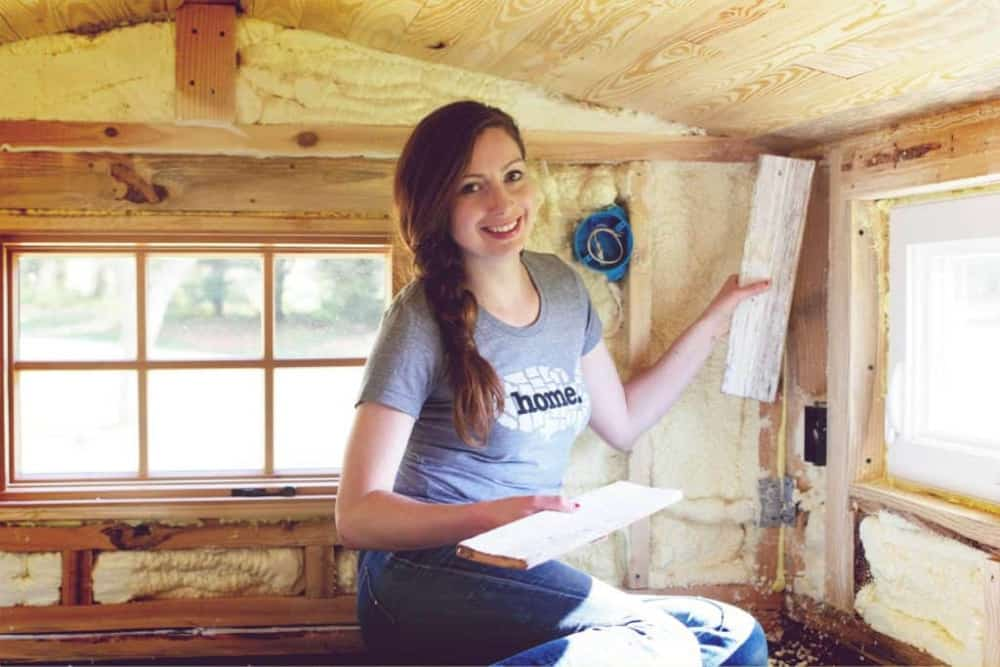 Woman holding up planks of wood while building her own DIY tiny house