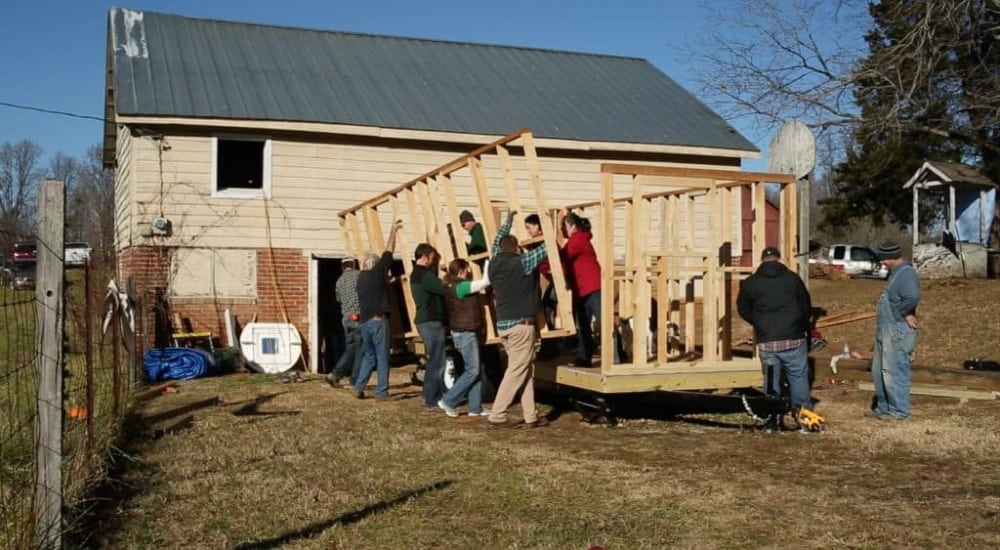 Group of people works together to lift wall of tiny house into place.