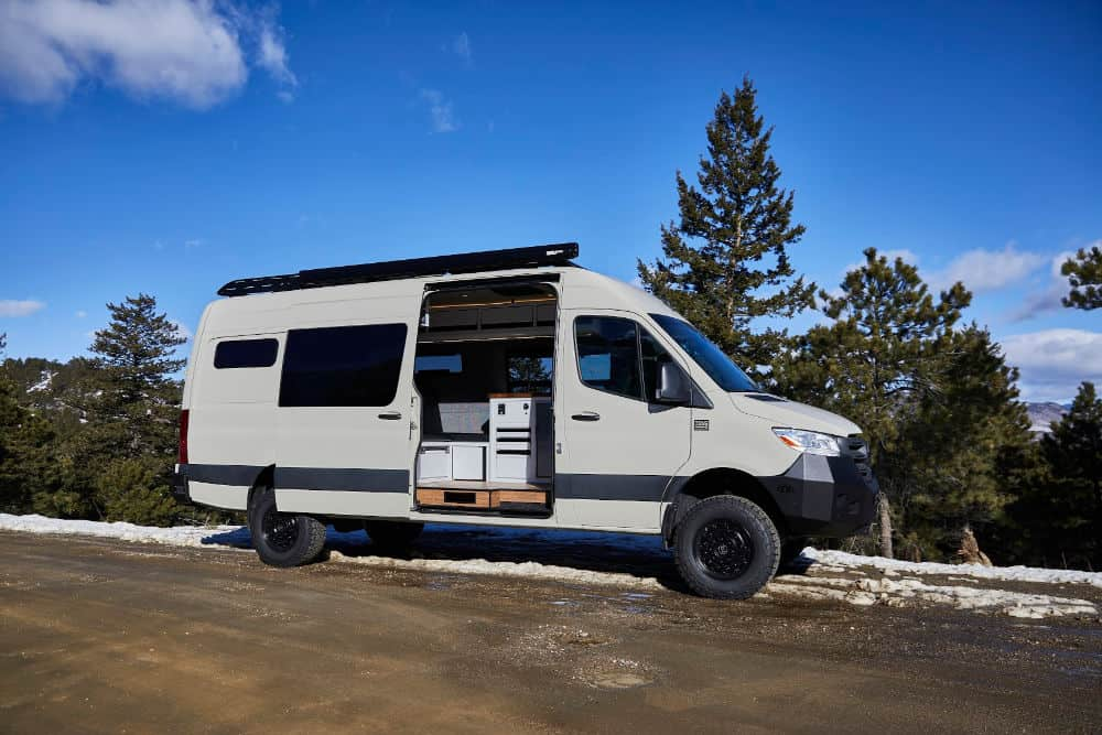 Sprinter van camper conversion with awning and side door open to reveal kitchen
