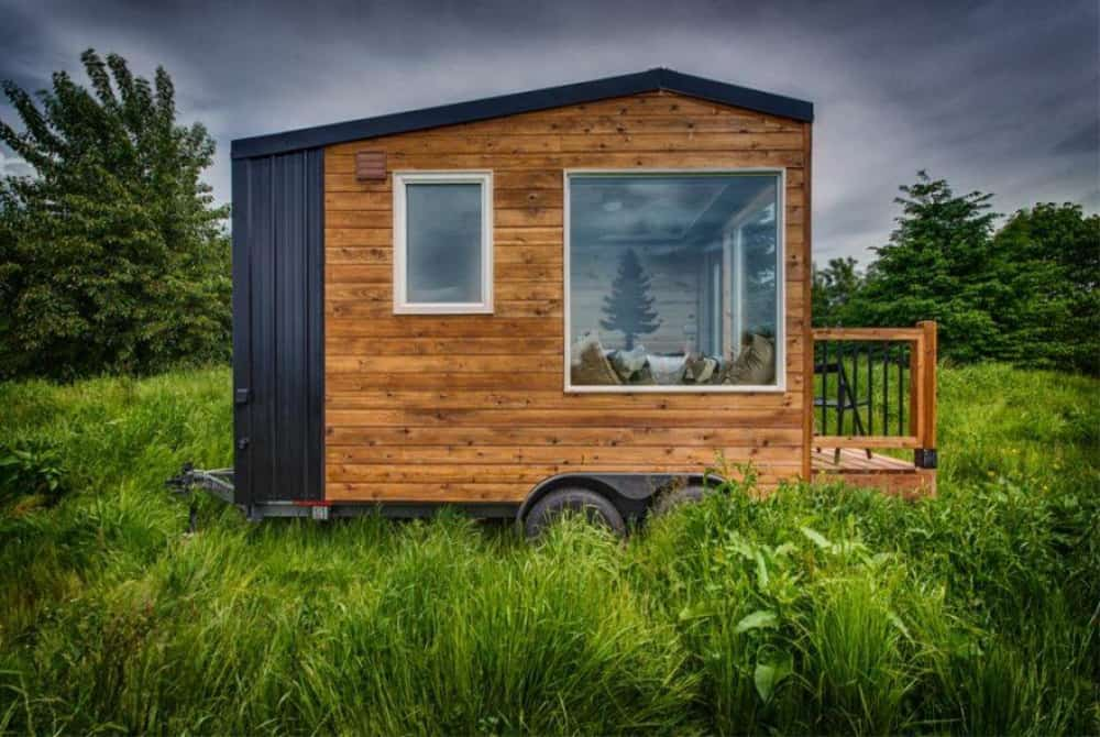 Side view of the acorn affordable tiny home with porch in a grassy field.