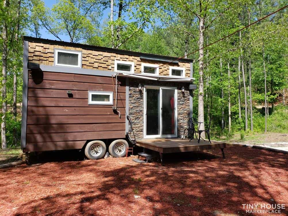 Custom cheap tiny house for sale has siding, shingles and faux stone exterior with porch and double glass doors.