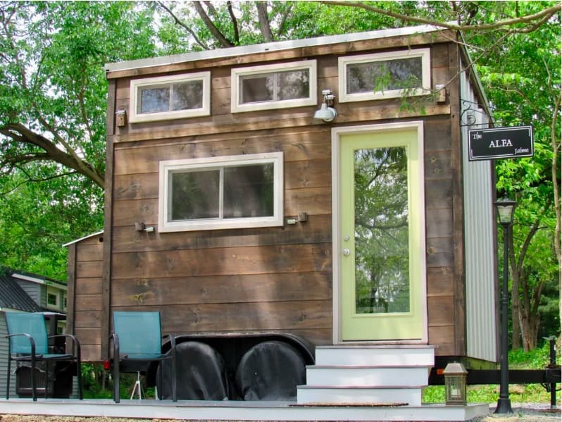 The modern, Alfa house affordable tiny home has white trim and horizontal wood siding.