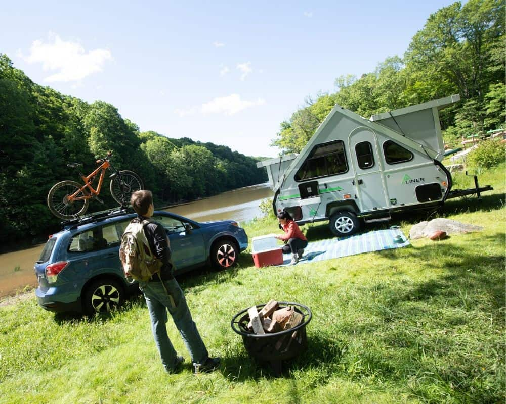 Aliner pop up camper with bathroom  parked on the riverbank with campers preparing camp site.