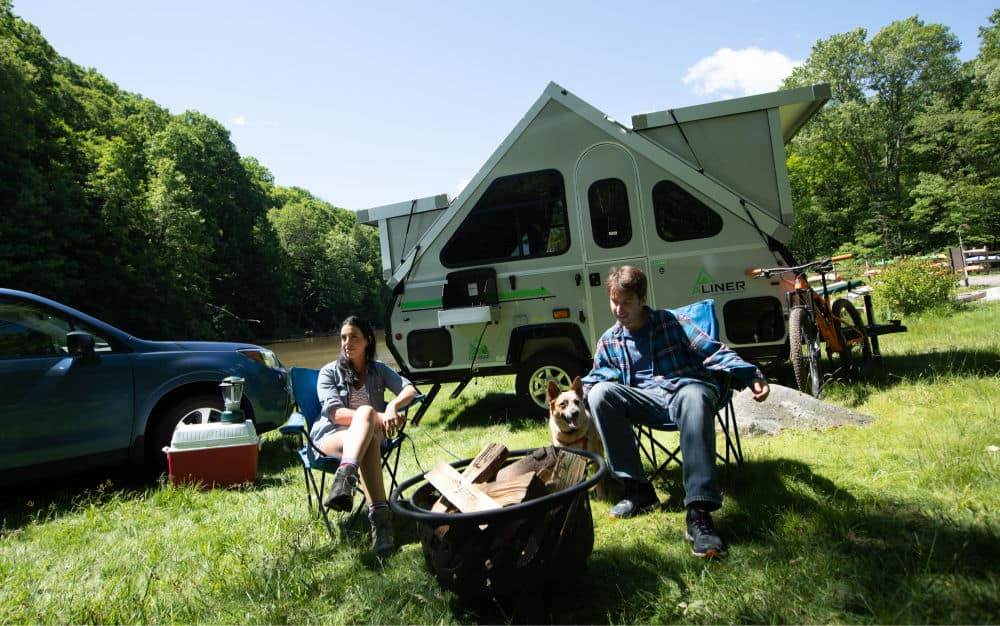 Two people sitting in front of an Aliner expedition A-frame camper