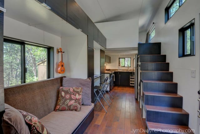 The interior of the hOMe tiny house plans with a couch and stairs leading to a loft