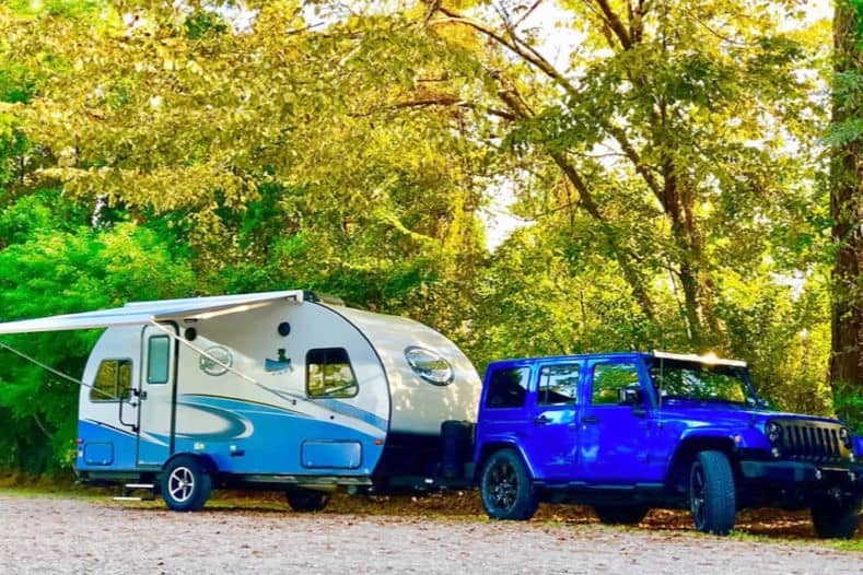 Blue Jeep towing an R-pod camping trailer with a bathroom