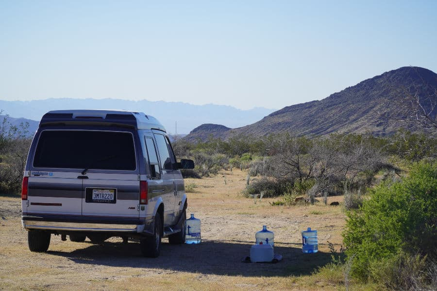 Astro van with three large jugs of water while boondocking in the Mojave desert