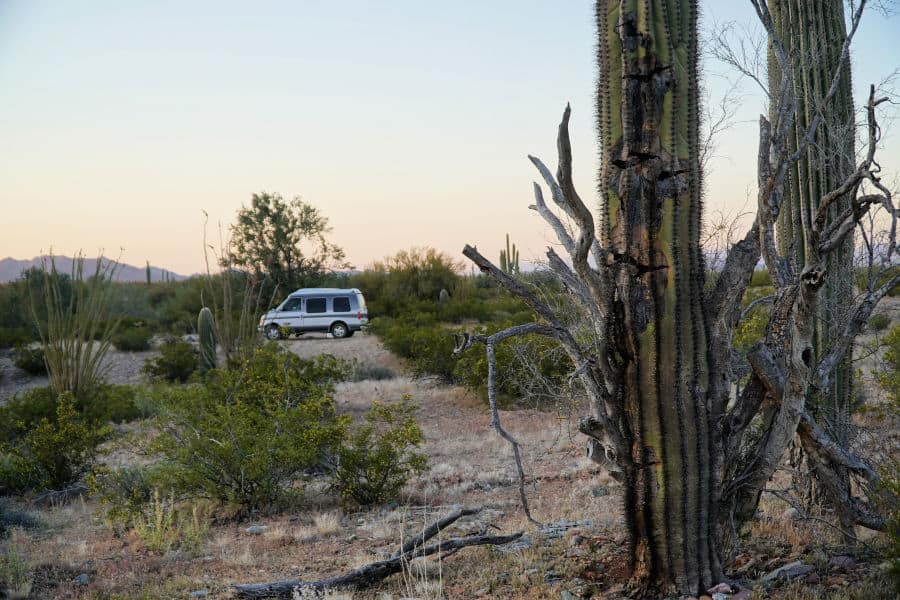 Campervan boondocking in the Sonoran Desert with saguaro cacti in the foreground.