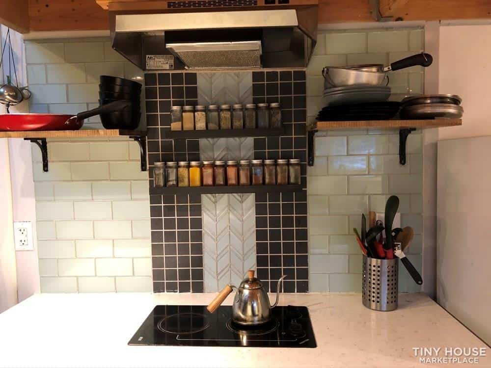 This affordable tiny home has lots of incredible details that make it really special, like the light green subway tile backsplash with herringbone detailing in the kitchen.