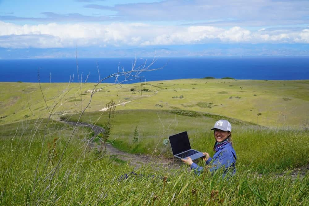 Me sending in remote freelance work sitting on top of a bright green hill