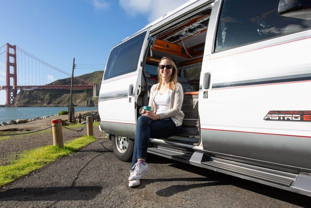 Woman sitting on the ledge of her Chevy Astro campervan, Golden Gate bridge in the background