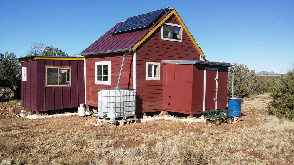 Off-grid tiny home with solar panels and attached rainwater catchment system sits on 10 acres in Arizona.